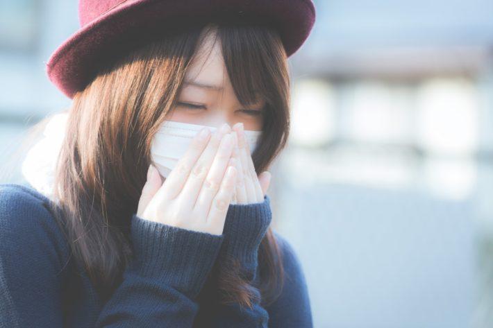 花粉症に苦しむマスク姿の女性