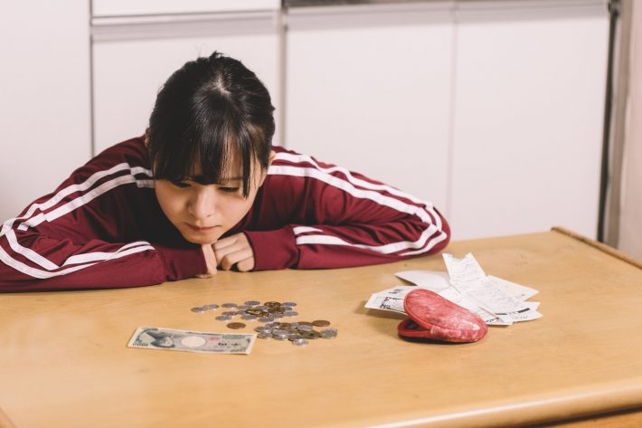 残ったお金を見つめるジャージ姿の節約ガール