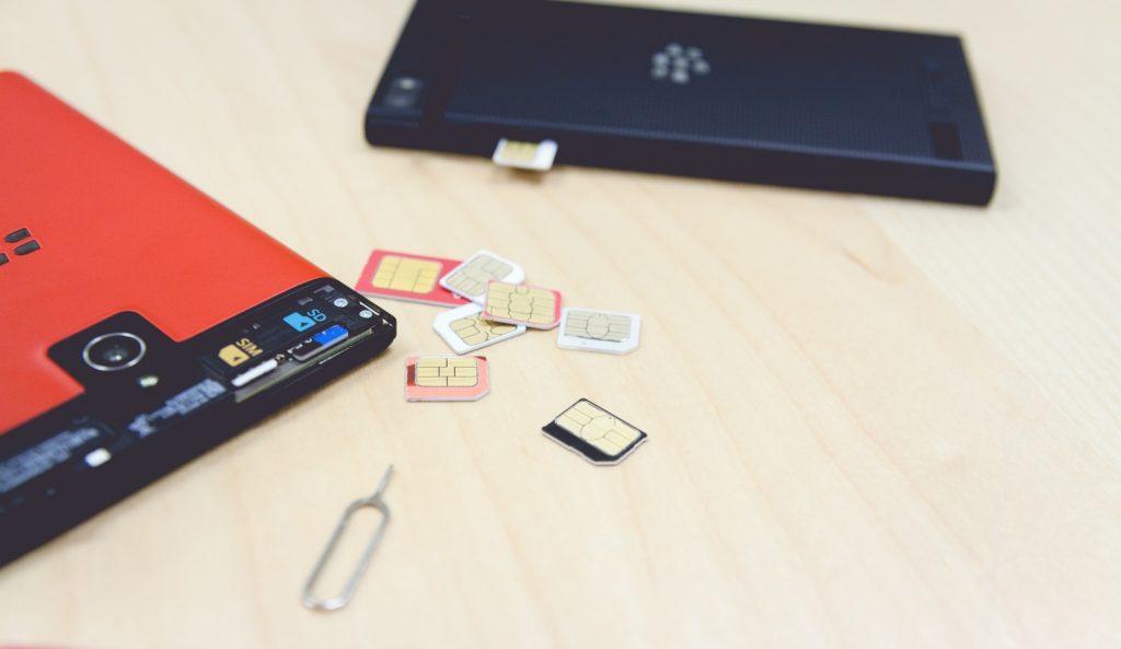 散らばったSIMカードとSIMカードを交換中のスマートフォン