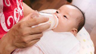 哺乳瓶を咥える新生児