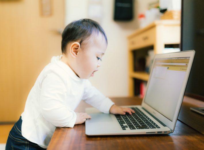 パソコンで手続きしている赤ちゃん
