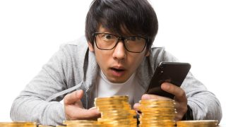 スマートフォンでトレードしている男性と金貨