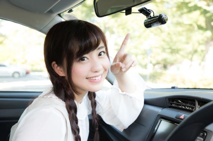 ドライブレコーダーを指差す可愛い彼女